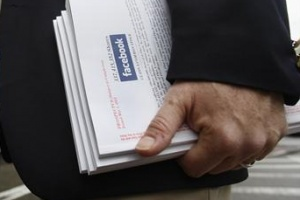 An investor holds literature explaining the Facebook stock after attending a show for Facebook Inc's initial public offering at the Four Season's Hotel in Boston, Massachusetts on May 8, 2012. REUTERS/Jessica Rinaldi