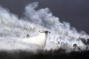 A helicopter drops water on the Waldo Canyon fire burning behind the U.S. Air Force Academy, west of Colorado Springs, Colorado June 27, 2012.   REUTERS/Rick Wilking