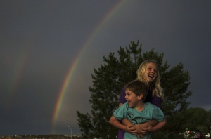 Siblings Alanna Jochim, 8, and Jared Jochim (front), 4, of Houston, Texas, play in front of a rainbow after a heavy rain fall in Colorado Springs, Colorado July 3, 2012. REUTERS/Adrees Latif