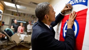 President Barack Obama autographs a banner while visiting a wounded service member at Walter Reed National Military Medical Center in Bethesda, Maryland, in this June 28, 2012, photograph. REUTERS/Pete Souza/Handout