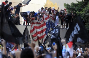 Protesters destroy an American flag pulled down from the U.S. embassy in Cairo September 11, 2012. Egyptian protesters scaled the walls of the U.S. embassy on Tuesday, tore down the American flag and burned it during a protest over what they said was a film being produced in the United States that insulted Prophet Mohammad. REUTERS/Mohamed Abd El Ghany