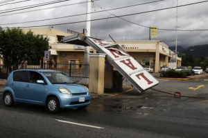 A supermarket sign lies at the entrance after it was blown down by Hurricane Sandy in Kingston, Jamaica.  REUTERS/Gilbert Bellamy