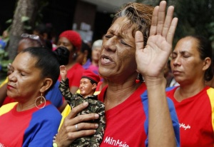 A woman holds a figurine of Venezuelan President Hugo Chavez, as she attends a mass to pray for Chavez's health in Caracas December 11, 2012.      REUTERS/Carlos Garcia Rawlins