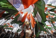 A woman dressed as Mother India poses with national flags during the country's Independence Day celebrations in Hyderabad August 15, 2012. REUTERS/Krishnendu Halder/Files