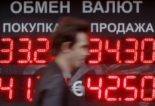 A man passes by a sign with currency exchange rates in Moscow June 4, 2012.  REUTERS/Denis Sinyakov