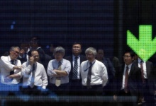 Businessmen are reflected in an electronic board displaying a downward arrow for the Nasdaq index outside a brokerage in Tokyo May 25, 2010. REUTERS/Yuriko Nakao