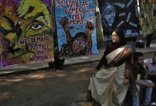 A demonstrator stands on a pavement near paintings by other demonstrators, as she listens to a speaker during a protest near parliament in New Delhi February 21, 2013. REUTERS/Adnan Abidi