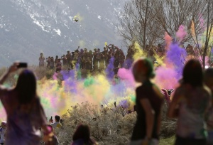 Spectators watch as participants dance and throw colored chalk during the Holi Festival of Colors at the Sri Sri Radha Krishna Temple in Spanish Fork, Utah, March 30, 2013. According to organizers 50,000 people were expected pack the temple grounds to celebrate Holi, the passing of winter to spring, and throw colorful powder throughout the day. REUTERS/Jim Urquhart