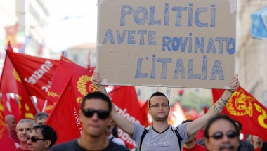 A member of Italy's metalworkers union Fiom holds up a placard during a demonstration in Rome, May 18, 2013. The placard reads, &quot;Politicians you bankrupt Italy.&quot; REUTERS/ Stefano Rellandini 
