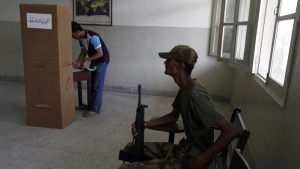 An army soldier (R) sits on a chair while a voter stamps his ballot papers inside a booth at a polling station during a re-polling for the general elections in Karachi, May 19, 2013. REUTERS/Akhtar Soomro