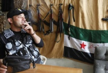 A member of the Free Syrian Army smokes near weapons displayed for sale inside a shop in the al-Myassar neighborhood of Aleppo May 20, 2013. REUTERS/Hamid Khatib
