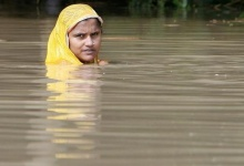 A flood-affected woman stands at a water logged road as she waits for relief supplies at Koran Tola village of Malda district in West Bengal August 25, 2009. REUTERS/Rupak De Chowdhuri/Files