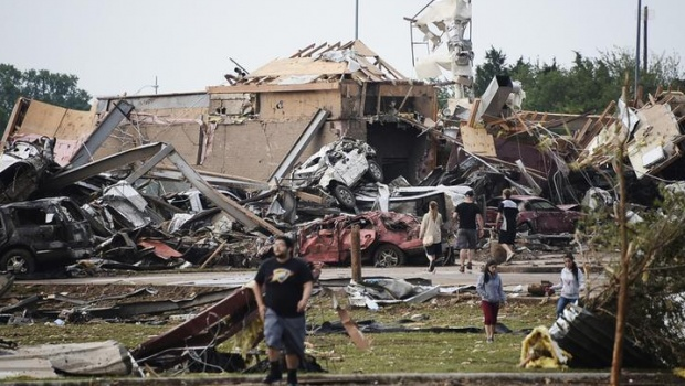 People walk near destroyed buildings and vehicles after a tornado struck Moore, Oklahoma, near Oklahoma City, May 20, 2013. REUTERS/Gene Blevins