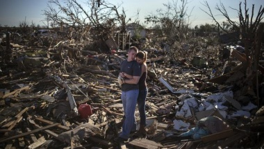 Danielle Stephan holds boyfriend Thomas Layton as they pause between salvaging through the remains of a family member's home one day after a tornado devastated the town Moore, Oklahoma, in the outskirts of Oklahoma City May 21, 2013. Rescuers went building to building in search of victims and thousands of survivors were homeless on Tuesday after a massive tornado tore through the Oklahoma City suburb of Moore, wiping out whole blocks of homes and killing at least 24 people.  REUTERS/Adrees Latif