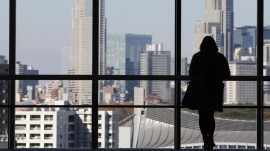 A woman looks at highrise buildings in Tokyo December 13, 2012.  REUTERS/Yuriko Nakao