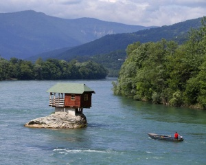 A man rows a boat near a house built on a rock on the river Drina near the western Serbian town of Bajina Basta, about 160km (99 miles) from the capital Belgrade May 22, 2013.  The house was built in 1968 by a group of young men who decided that the rock on the river was an ideal place for a tiny shelter, according to the house's co-owner, who was among those involved in its construction.  REUTERS/Marko Djurica