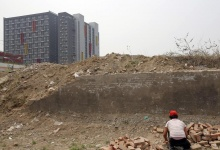 A woman collects bricks at a demolition site, where an old village is making way for new buildings, on the outskirts of Beijing, May 23, 2013.  REUTERS/Kim Kyung-Hoon