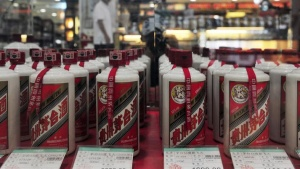 A customer walks past a glass case displaying Maotai liquors with different price tags at a supermarket in Shenyang, Liaoning province August 8, 2012.REUTERS/Stringer