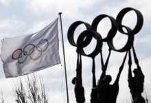 A sculpture is pictured in front of a flag at the International Olympic Committee (IOC) headquarters in Lausanne March 18, 2008. REUTERS/Denis Balibouse