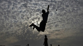 Boys play cricket on the Marina beach in Chennai May 24, 2013. REUTERS/Babu