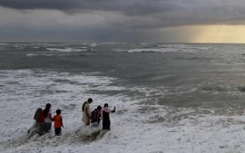 Beachgoers walk in the waters at Fort Kochi beach as clouds hover over the Arabian Sea in Kerala May 23, 2013. REUTERS/Sivaram V