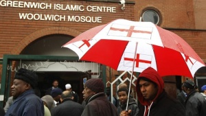 A man with a St George flag umbrella walks among worshippers leaving the Woolwich Mosque after Friday prayers in Woolwich, southeast London May 24, 2013. REUTERS/Luke MacGregor