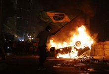 A demonstrator waves a Brazilian flag by a burning a car in downtown Rio de Janeiro June 17, 2013. REUTERS/Sergio Moraes