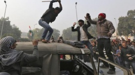 A demonstrator breaks the windshield of a police vehicle as others shout slogans in front of the India Gate during a protest in New Delhi December 23, 2012. REUTERS/Ahmad Masood/Files