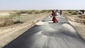 Women labourers throw dust on a road tarmac under construction at Bharadva village in Gujarat April 23, 2013. REUTERS/Amit Dave/Files