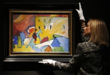 A Christie's employee poses with  Wassily Kandinsky Studie zu 'Improvisation at Christie's auction house in London June 7, 2013.  REUTERS/Luke MacGregor