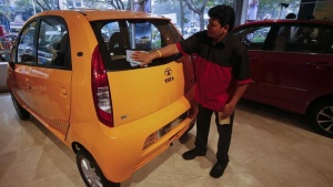 A showroom attendant cleans a Tata Nano car at the flagship Tata Motors showroom in Mumbai February 14, 2013. REUTERS/Vivek Prakash/Files
