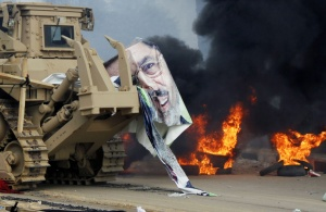 A torn poster of deposed Egyptian President Mohamed Mursi is pictured as riot police clear the area of his supporters at Rabaa Adawiya square, where the protesters had been camping, in Cairo August 14, 2013. REUTERS/Mohamed Abd El Ghany