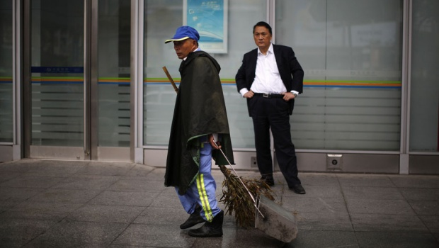 Dai Yusheng (front), 58, who works as an employee sweeping the streets of the Shanghai's Hongkou district, walks near a shopping mall during a rainy day May 31, 2013. Dai works as a cleaning personnel for a company that is contracted by Shanghai Municipal government. He makes 14RMBs per hour ($US2.28). He usually works from 4am in the morning to 1pm 6 days a week. Dai and his wife rent a 3x4 meter room at a slam near his work area. REUTERS/Carlos Barria