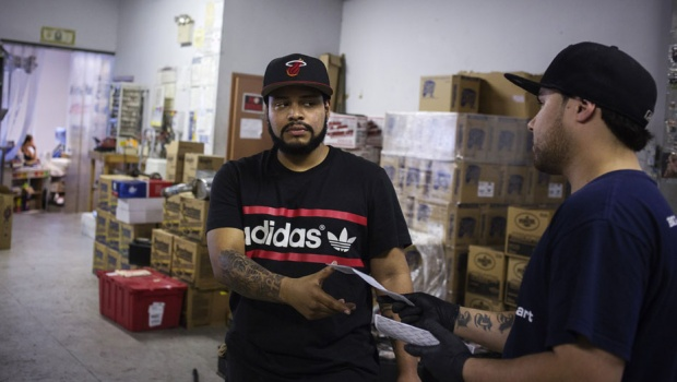 Javier Alava, 27, receives his check for working at an auto store in Long Island, New York, May 30, 2013. Alava works for an auto store and makes just above the national minimum wage, not exceeding eight dollars an hour. Alava commutes daily from Brooklyn by subway to Long Island which takes him about an hour. REUTERS/Shannon Stapleton