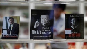 A man reads a book at the Thaksin Shinawatra library at the Puea Thai Party headquarters in Bangkok October 29,2012. REUTERS/Sukree Sukplang/Files