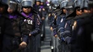 Policemen wear their riot gear inside the compound of the prime minister's office, known as the Government House, as anti-government protesters gather behind its fence and gates in Bangkok December 12, 2013. REUTERS/Damir Sagolj