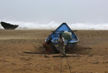 Fishermen tie their boat along the shore before leaving for a safer place at Donkuru village in Srikakulam district, in Andhra Pradesh October 12, 2013. REUTERS/Adnan Abidi/Files