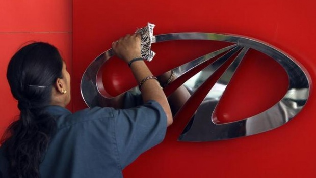 A worker cleans a logo of Mahindra & Mahindra inside their showroom in Chennai April 12, 2011. REUTERS/Babu/Files