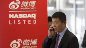 Weibo Corporation Chairman Charles Chao talks on a cell phone before the opening of trading for Weibo at the NASDAQ MarketSite in Times Square on day one of its initial public offering (IPO) on The NASDAQ Stock Market in New York April 17, 2014. REUTERS/Andrew Kelly