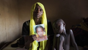 Rachel Daniel, 35, holds up a picture of her abducted daughter Rose Daniel, 17, as her son Bukar, 7, sits beside her at her home in Maiduguri in this May 21, 2014 file photo. REUTERS/Joe Penney/Files