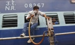A man washes his face using a pipe that supplies water to trains at a railway station on a hot summer day in Allahabad June 9, 2014. REUTERS/Jitendra Prakash