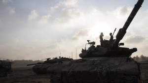 Israeli soldiers stand atop a tank, just outside the Gaza Strip July 22, 2014.  REUTERS/Baz Ratner