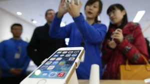 A staff of a China Mobile shop explains a function of the iPhone 5s to a customer in Beijing January 17, 2014. REUTERS/Kim Kyung-Hoon/Files