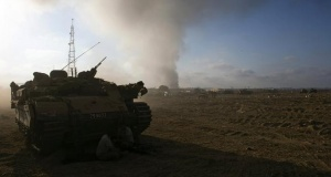 Smoke rises after an explosion in Gaza as an Israeli armoured personnel carrier (APC) is parked at a staging area near the border with Gaza July 23, 2014. REUTERS/Ronen Zvulun