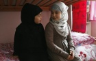 Sanaa, 10, and her sister Israa, 7, get ready for Islamic school in Leyton, east London November 9, 2013. REUTERS/Olivia Harris/Files