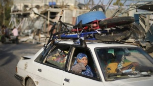 A Palestinian woman sits in a car on her way home after a ceasefire was declared, in Beit Hanoun town in the northern Gaza Strip August 27, 2014. REUTERS/Suhaib Salem