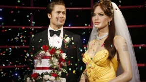 Wax models of actors Brad Pitt and Angelina Jolie have confetti thrown on them after being presented with a wedding cake and bridal veil in celebration of their recent wedding, at the Madame Tussauds attraction in Sydney, August 29, 2014. REUTERS/Jason Reed