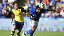 Arsenal's Mesut Ozil (L) fights for the ball with Leicester City's Liam Moore during their English Premier League soccer match at the King Power Stadium in Leicester, northern England August 31, 2014. REUTERS/Dylan Martinez