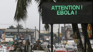 A U.N. convoy of soldiers passes a screen displaying a message on Ebola on a street in Abidjan August 14, 2014. REUTERS/Luc Gnago/Files