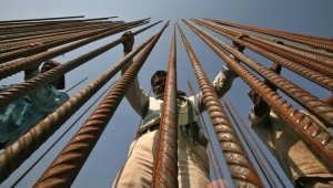 Workers hold iron rods at the construction site of a bridge on the river Tawi in Jammu November 30, 2011.REUTERS/Mukesh Gupta